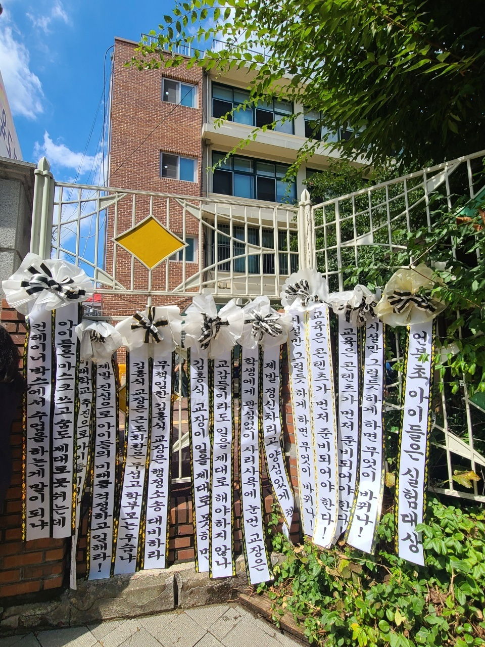 Fences at Seoul Eonbuk Elementary School in Gangnam-gu, Seoul, are covered with ribbons normally used to decorate funeral wreaths, Wednesday. (Reader submission)