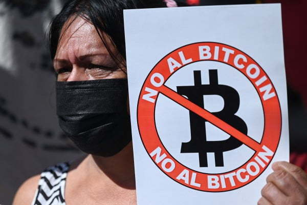 A woman holds a placard which reads `No to Bitcoin` during a protest on Tuesday. (AP/Yonhap)