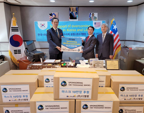Liberia's honorary consul general Park Bok-woo (left) and DL Pharm chief executive Kang Yoon-koo (center) pose for photos to mark the firm's donation of facial masks to the African country. (DL Pharm)
