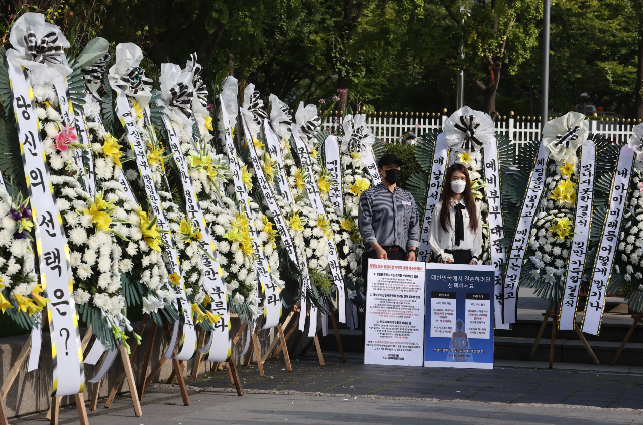Members of an association of newlyweds protest the social distancing measures applied to weddings outside the government complex in Seoul on Thursday. (Yonhap)
