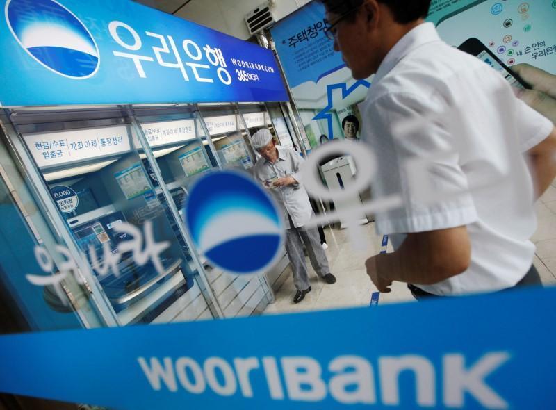 Two men stand by a Woori Bank ATM. (Yonhap)