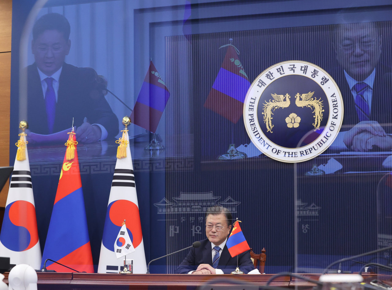 President Moon Jae-in attends a virtual summit with his Mongolian counterpart, Ukhnaagiin Khurelsukh (on screen), at Cheong Wa Dae on Friday. (Yonhap)
