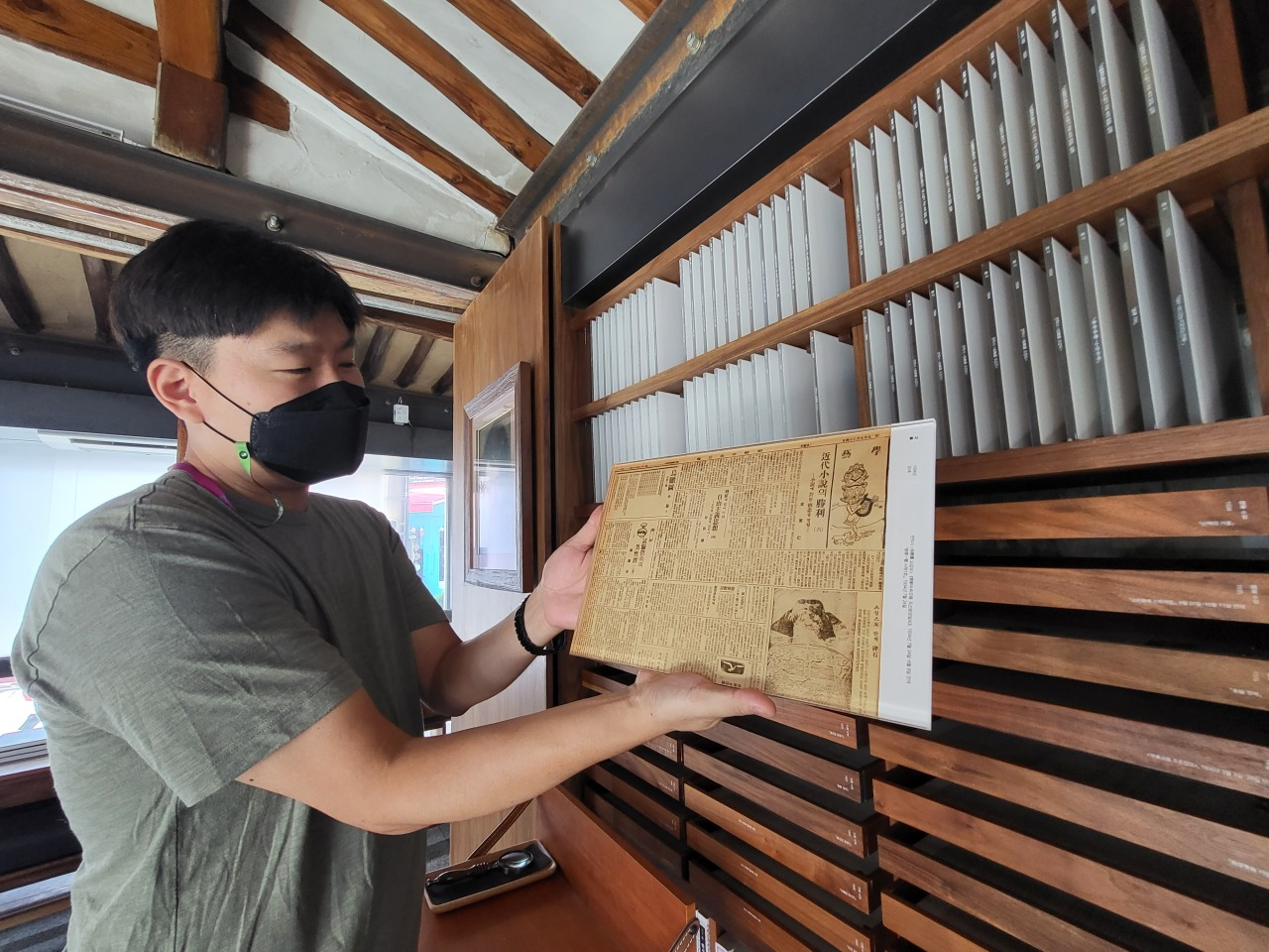 Lee Sang-hyun, who is in charge of publicity for the National Trust for Cultural Heritage, holds up a copy of one of Lee Sang's works from 1934. (Kim Hae-yeon/The Korea Herald)