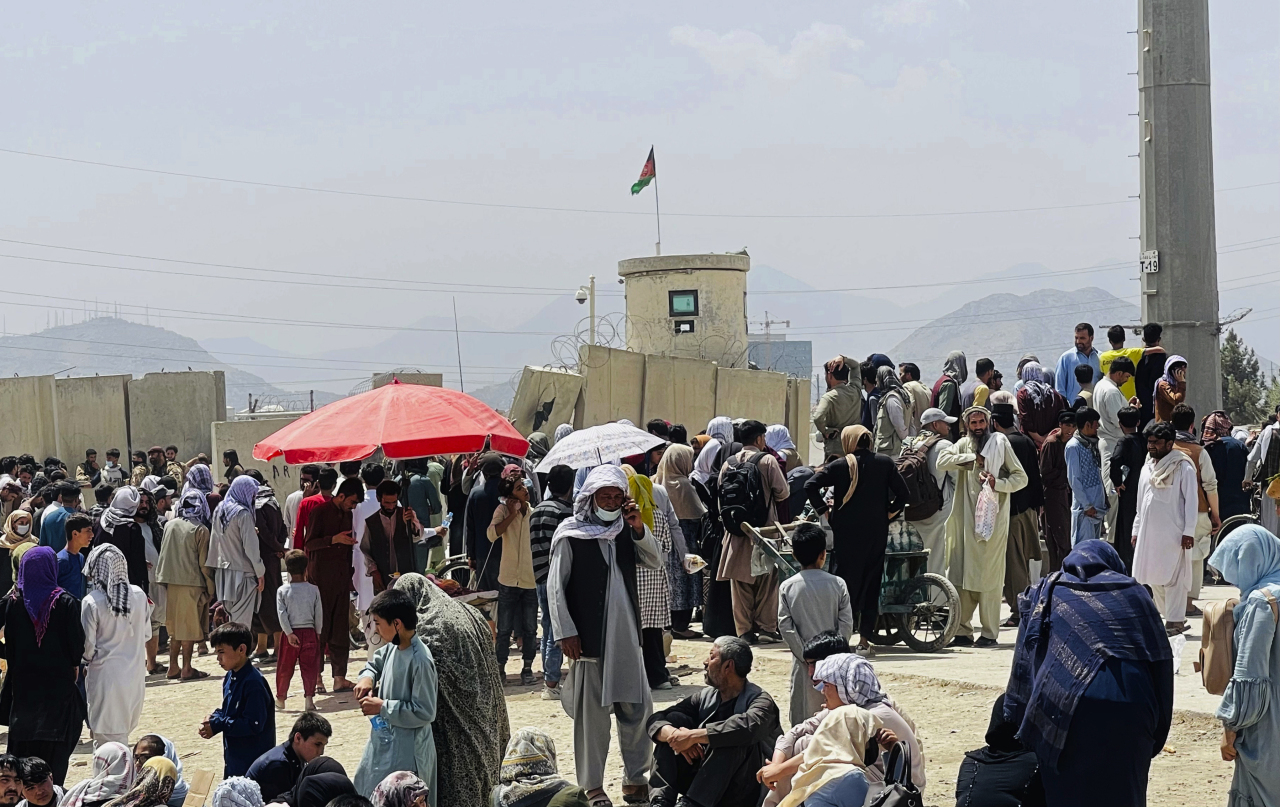 This file photo, released by the Associated Press on Aug. 17, 2021, shows people gathering outside the international airport in Kabul, Afghanistan. (Yonhap)