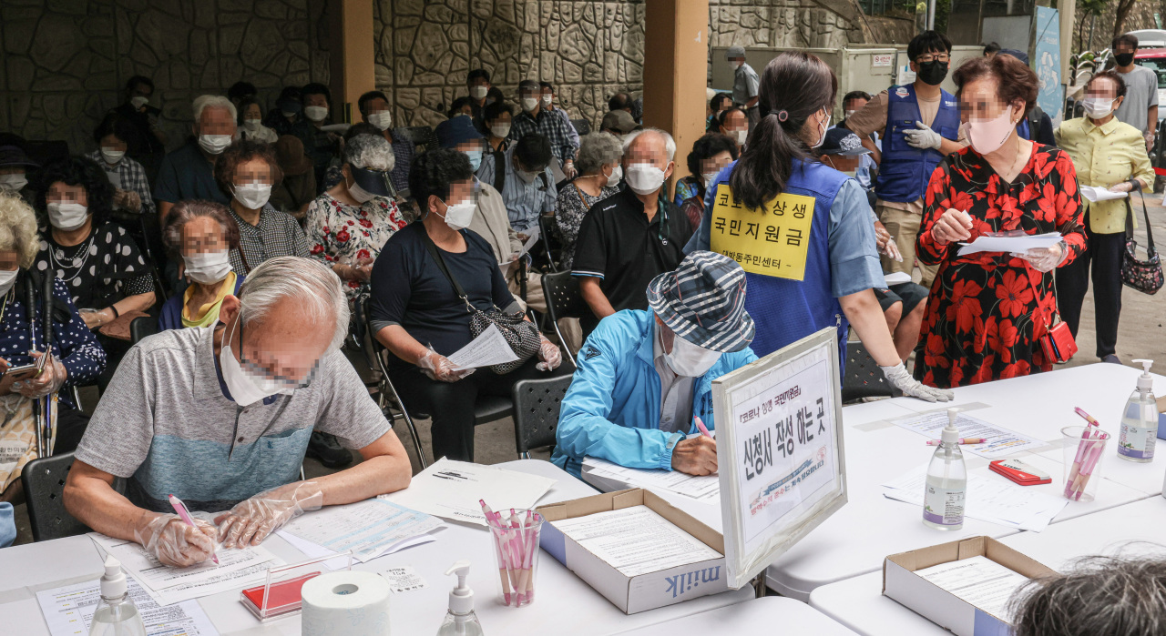 Senior citizens gathered to apply for COVID-19 pandemic relief funds at a community service center in Dongjak-gu, Seoul on Monday. (Yonhap)