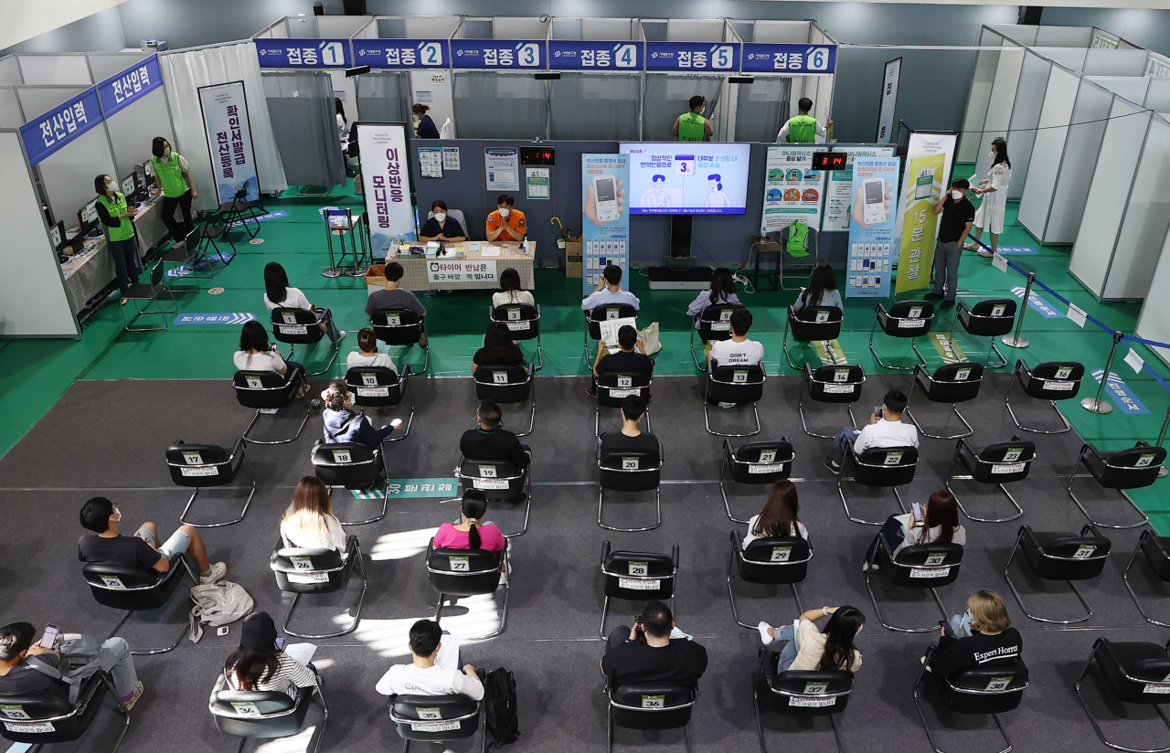 This photo taken on Monday, shows people waiting for COVID-19 vaccine shots at an inoculation center in Seoul. (Yonhap)