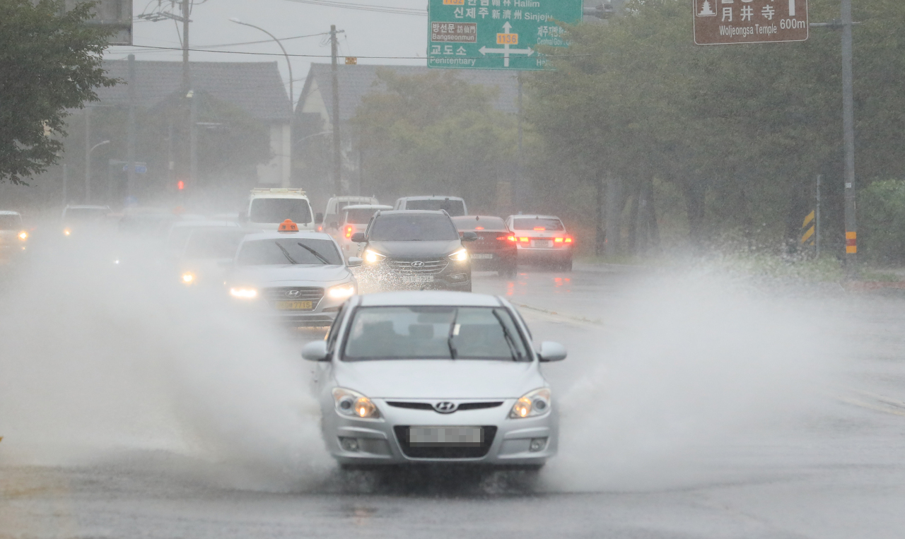 Cars run amid heavy downpours on Jeju, South Korea, on Tuesday. (Yonhap)