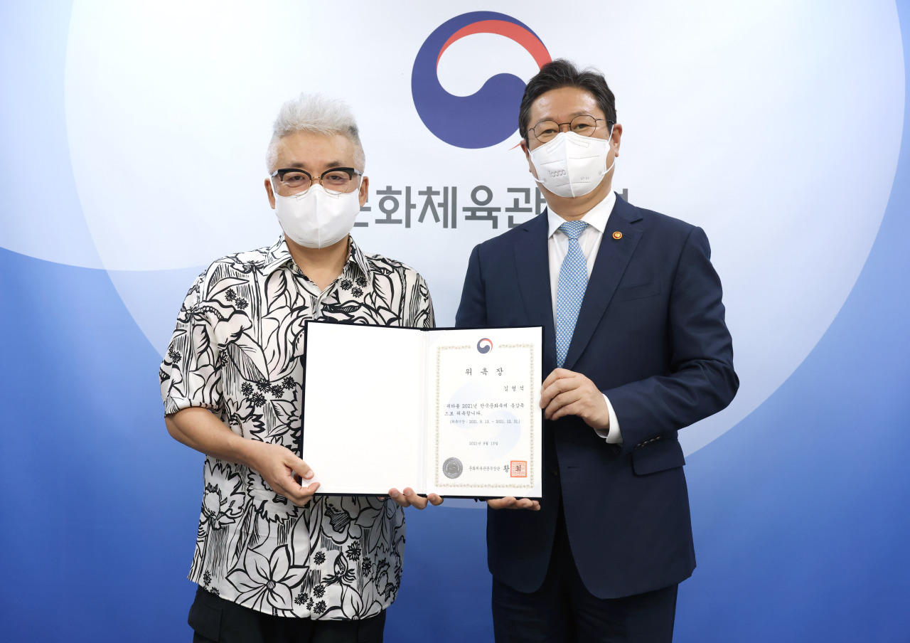Culture Minister Hwang Hee and music producer Kim Hyung-suk (left) pose for photos at the Culture Ministry's office in Yongsan, central Seoul, on Monday. (Yonhap)