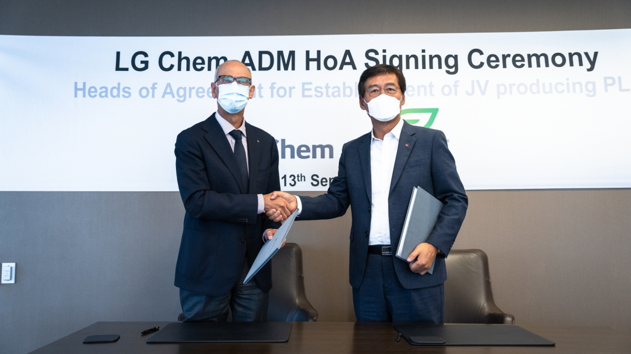 LG Chem Vice Chairman and CEO Shin Hak-cheol (right) and ADM Chairman and CEO Juan Luciano pose after signing an agreement at ADM's global headquarters in Chicago, Monday. The two will form a US joint venture to produce 75,000 tons of corn-based bioplastic per year starting 2025. (LG Chem)