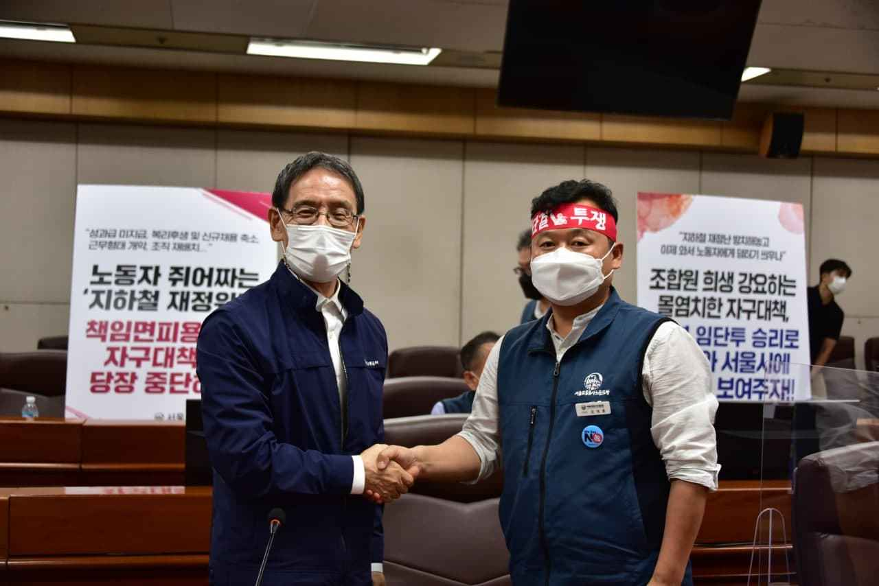 Seoul Metro CEO Kim Sang-bum (left) poses for a photo with Seoul Metro labor union head Kim Dae-hoon (right) after reaching an agreement over Seoul subway authority's restructuring plan. (Seoul Metro)