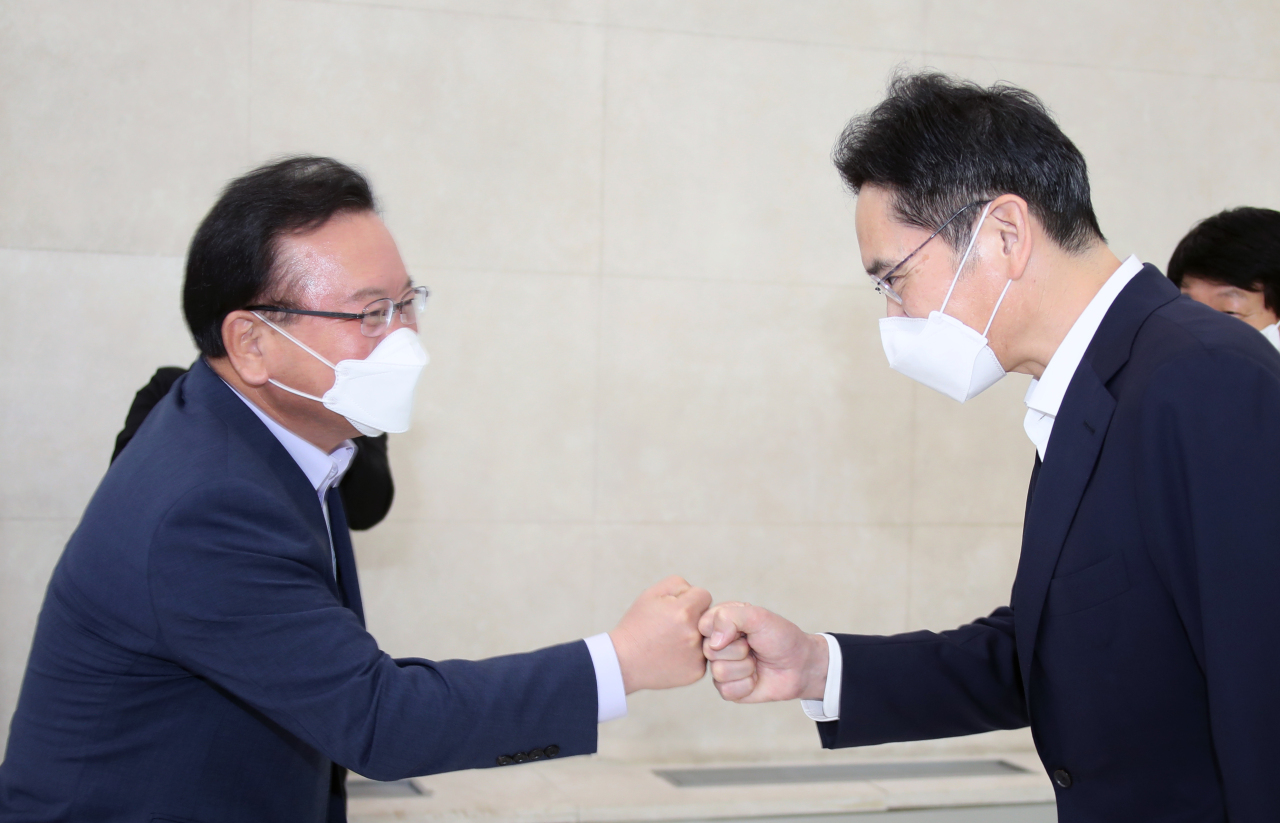 Prime Minister Kim Boo-kyum (L) bumps his fist with Lee Jae-yong, Samsung Electronics Co. vice chairman, when he visits the Samsung Software Academy For Youth (SSAFY), which offers a free one-year program of computer programming courses aimed at training young software engineers, in southern Seoul on Tuesday. (Yonhap)
