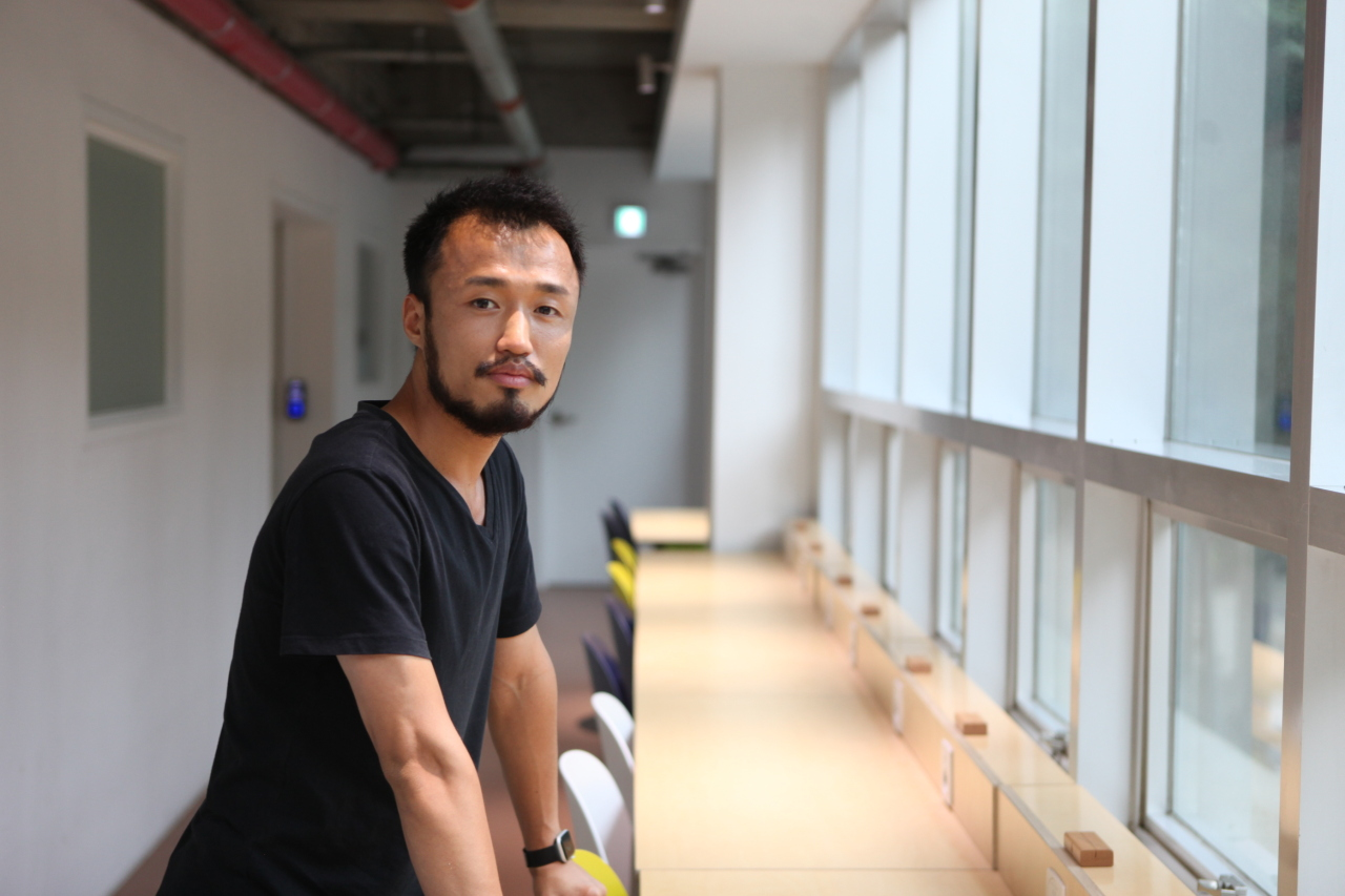 Kang Min, CEO of web development firm Godzebe, poses for a photo after an interview with The Korea Herald at his coworking space in Seoul. (Park Ga-young/ The Korea Herald)