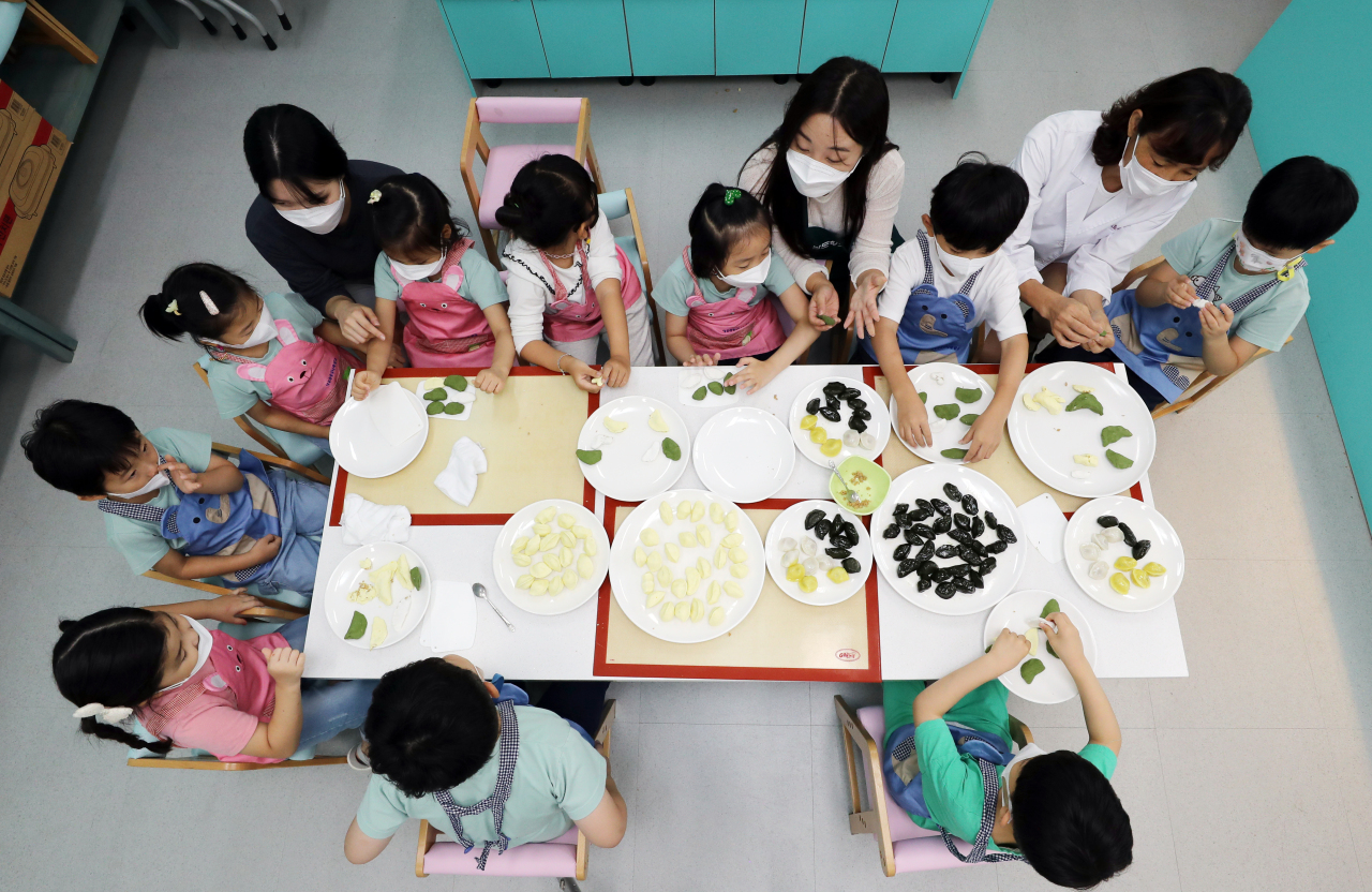 Children and teachers gather around a table with everything they need to make songpyeon. (Yonhap)