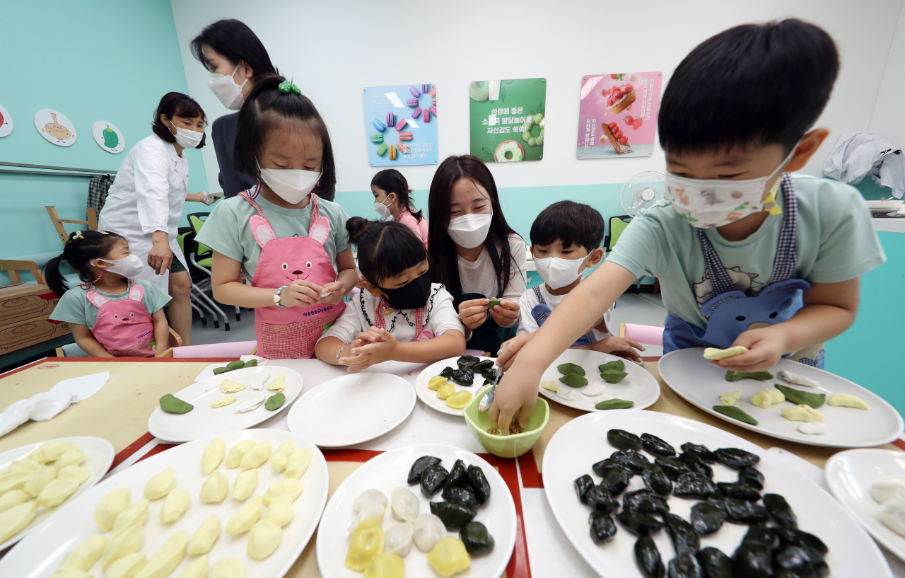 Children make songpyeon with help from their teachers. (Yonhap)