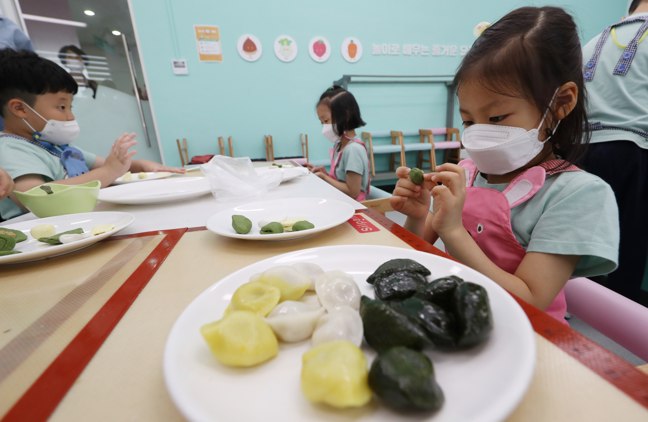 Children assemble ingredients and shape their songpyeon. (Yonhap)