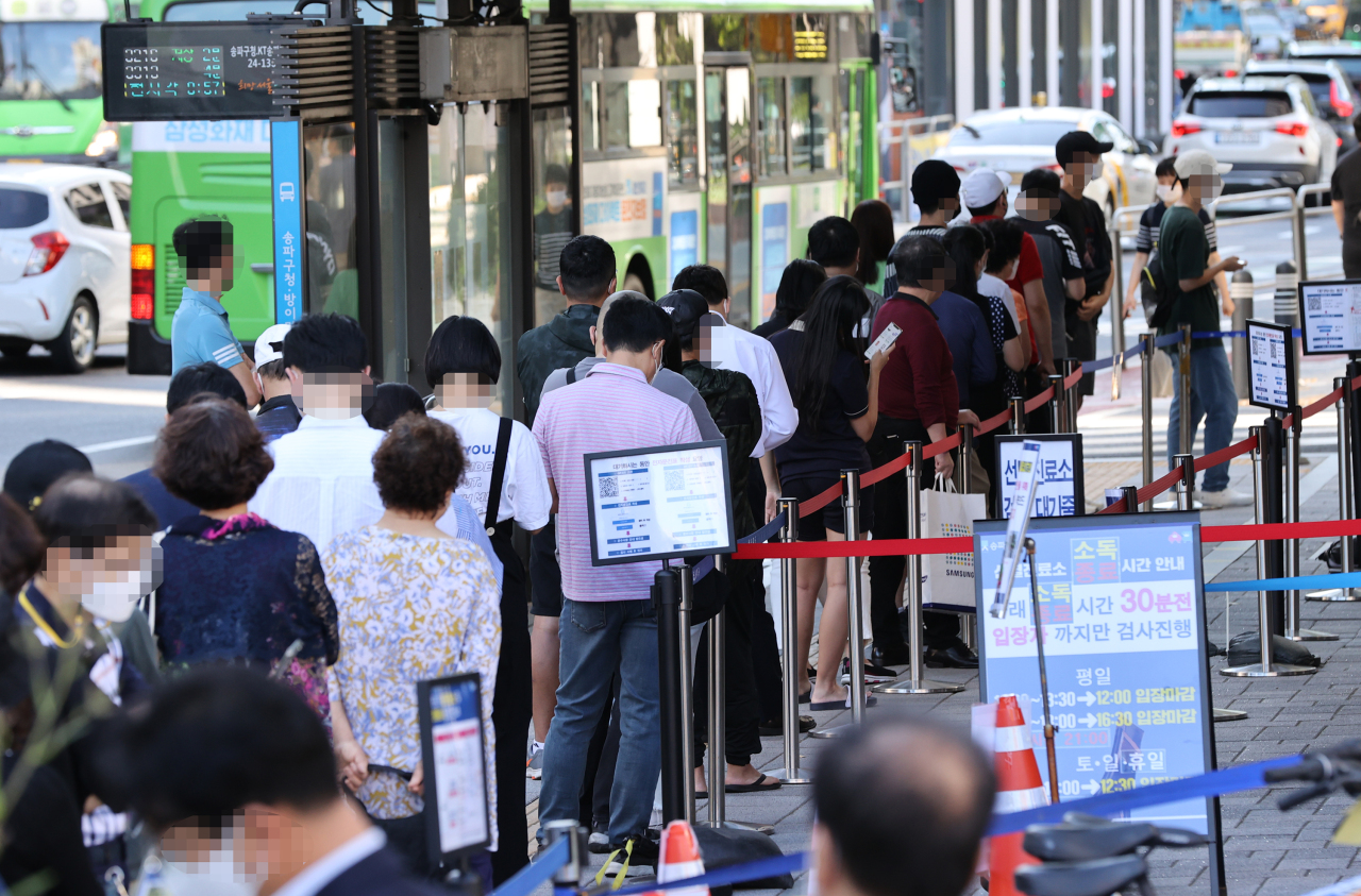 People wait in line to receive virus tests at a COVID-19 testing clinic in Seoul on Wednesday. (Yonhap)