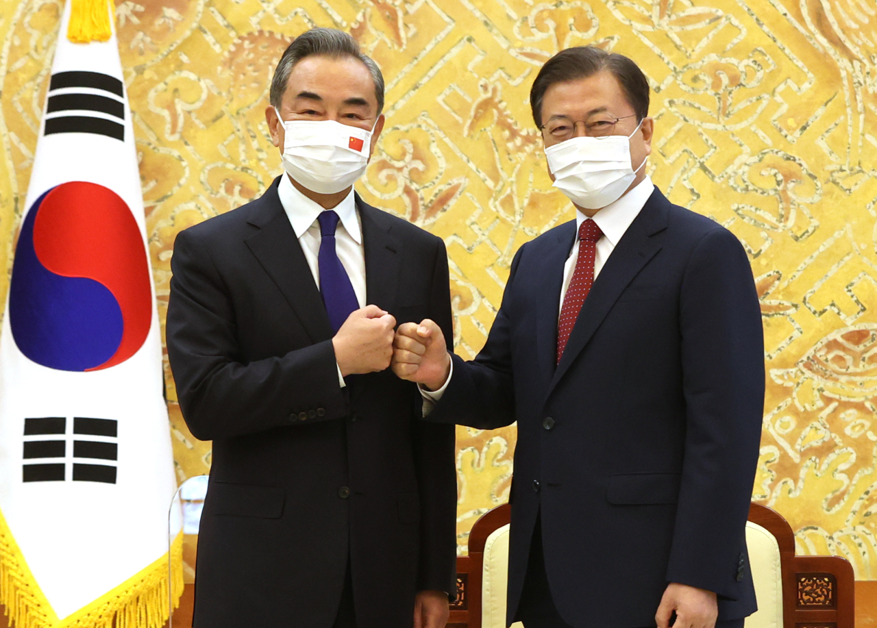 South Korean President Moon Jae-in (R) bumps fists with Chinese Foreign Minister Wang Yi during a meeting at Cheong Wa Dae in Seoul on Wednesday. (Yonhap)