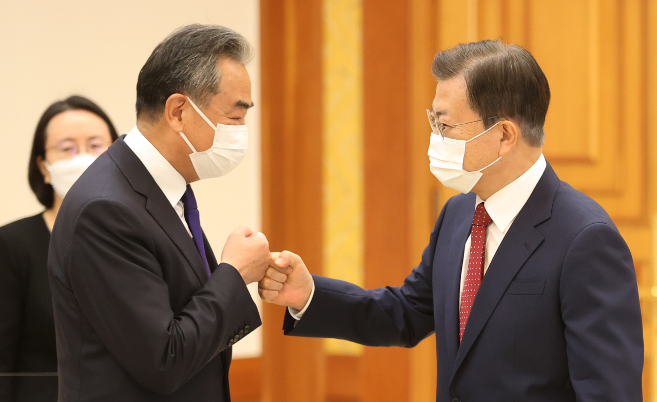 President Moon Jae-in greets Chinese Foreign Minister Wang Yi at Cheong Wa Dae in Seoul on Wednesday. (Yonhap)