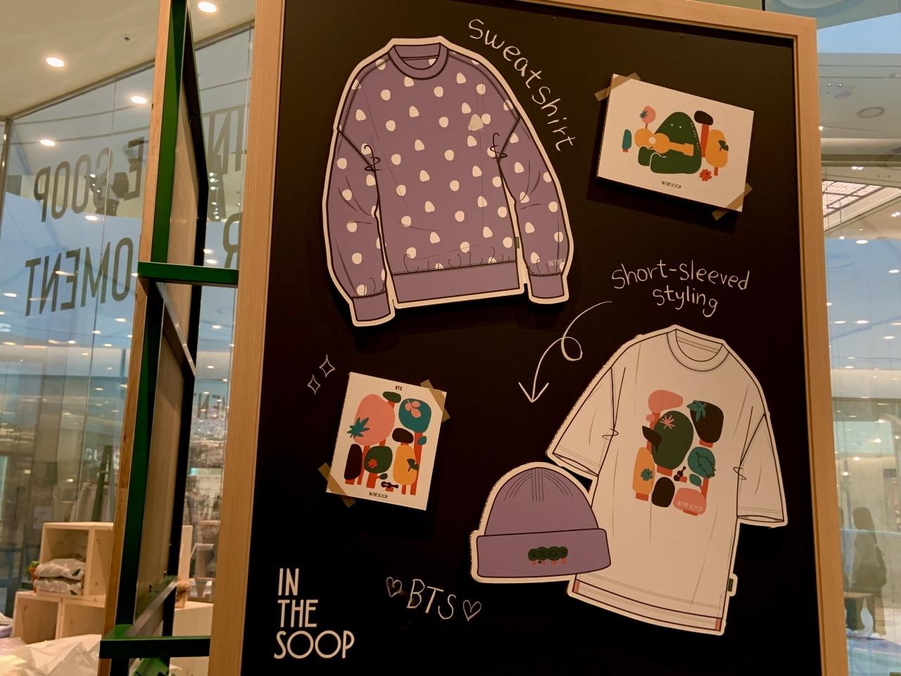 A blackboard features illustrations of BTS merchandise, including a sweatshirt and T-shirt. (Park Jun-hee/The Korea Herald)