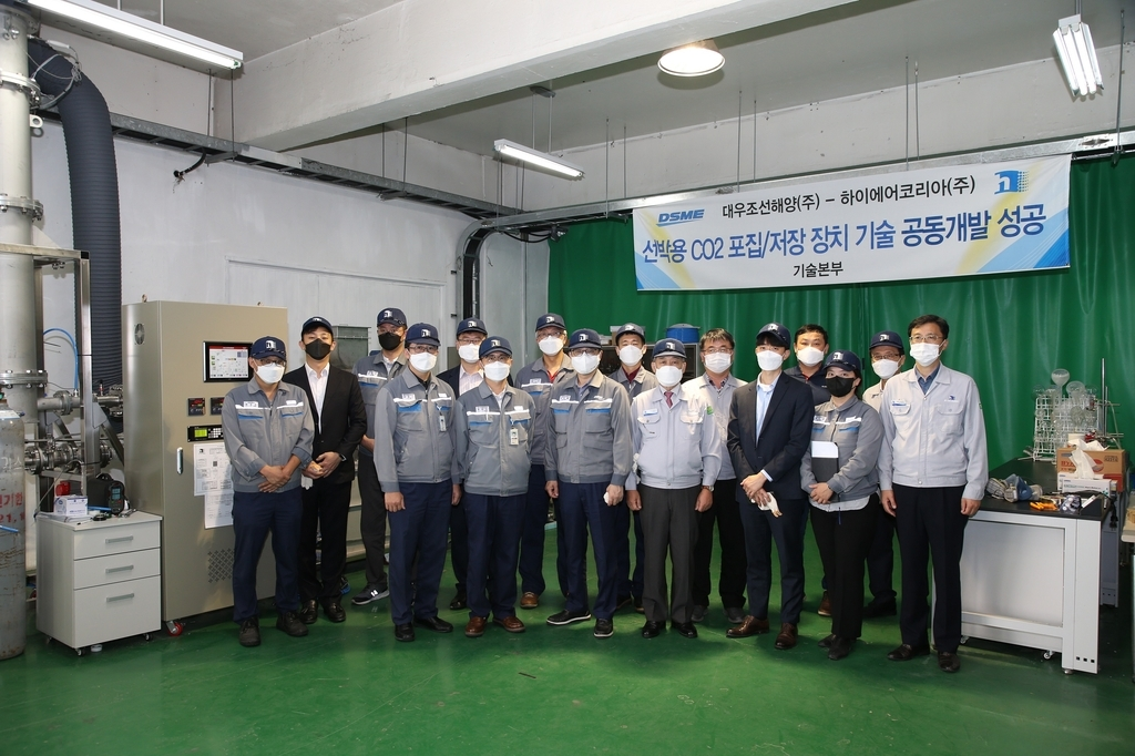 Workers from South Korea's shipbuilder Daewoo Shipbuilding & Marine Engineering Co. (DSME) and ship part supplier HI AIR Korea Co. pose for a picture after testing the technology to store carbon captured in ship engine emissions, in this photo provided by DSME on Thursday. (DSME)