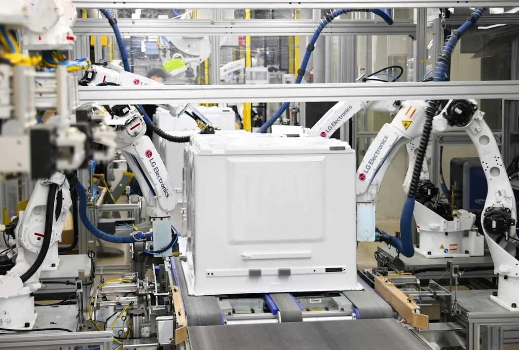 This photo provided by LG Electronics Inc. on Thursday, shows a robot assembling a refrigerator on a production line at LG Smart Park in Changwon, 400 kilometers south of Seoul. (LG Electronics Inc.)