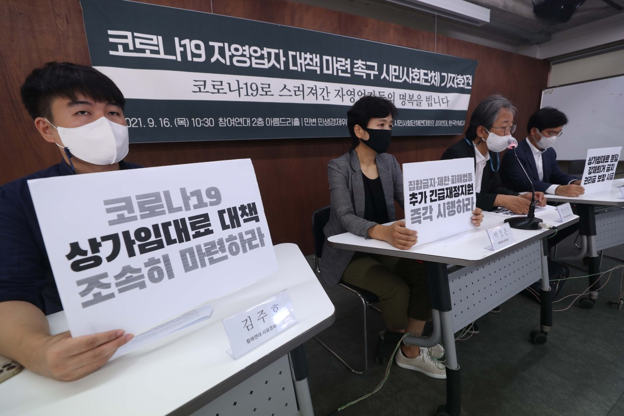 Activists hold signs at a press conference in Seoul, demanding the government come up with more support measures for small business owners and the self-employed hit hard by the pandemic on Thursday. (Yonhap)