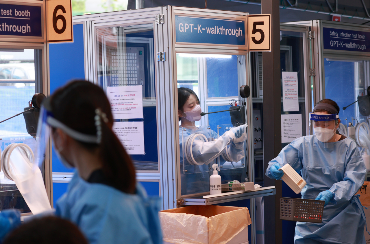 Health workers in protective gear work at a COVID-19 testing clinic in Seoul on Wednesday. (Yonhap)