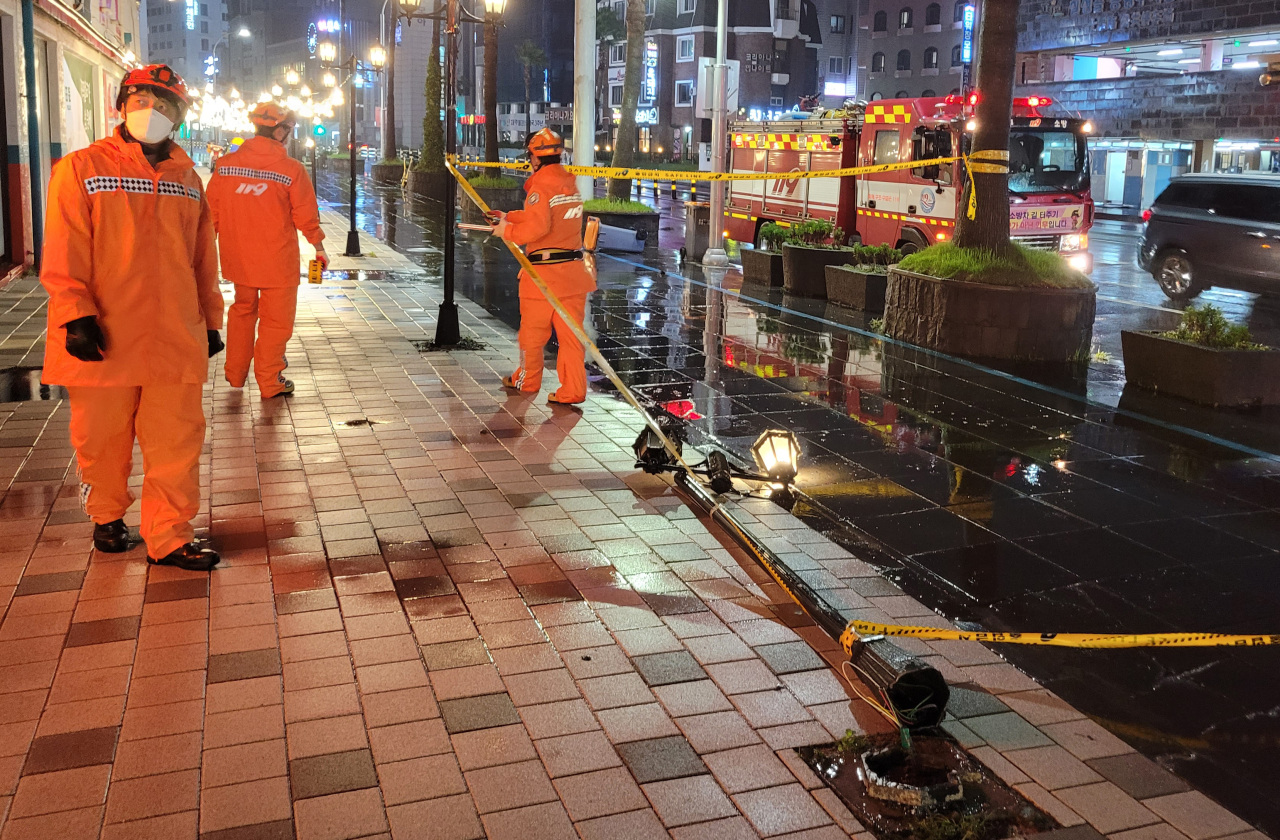 Firefighters respond to a downed streetlight in Jeju, South Korea, on Thursday, in this photo provided by the Jeju Fire Safety Headquarters. (Yonhap)