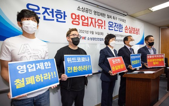 Members of the Korea Federation of Micro Enterprise hold a press conference at the National Assembly on Tuesday, to demand the government scrap antivirus restrictions and compensate them for business losses. (Yonhap)