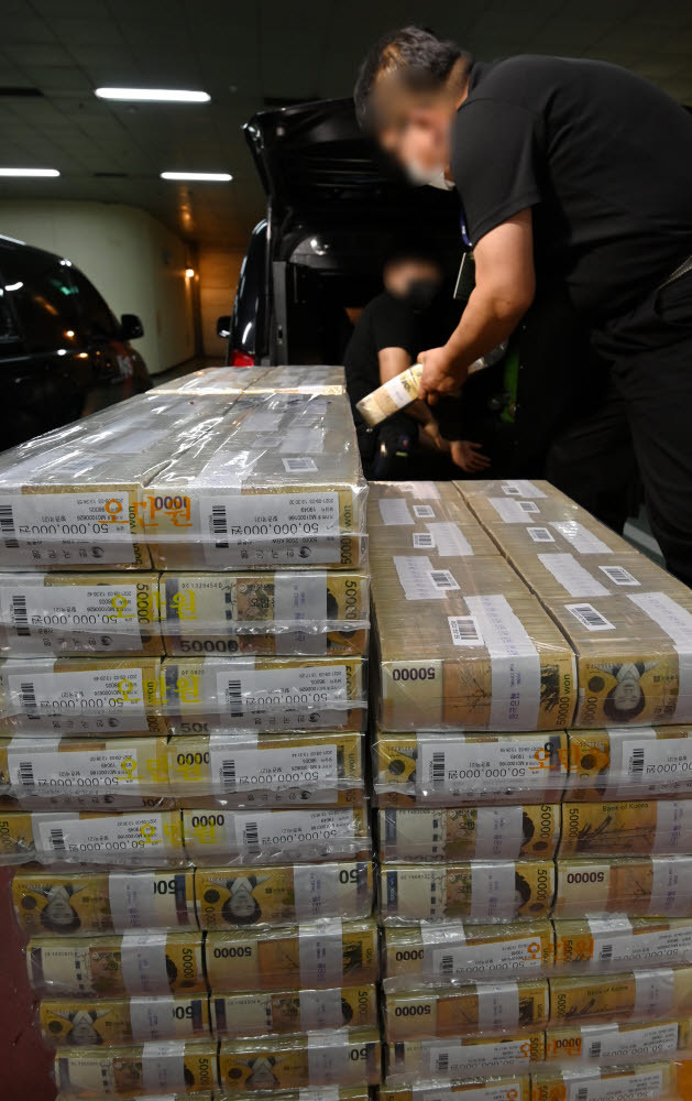 Security firm workers move bundles of cash at the Bank of Korea in Seoul on Thursday, as the central bank supplies funds to commercial banks to meet rising cash demand ahead of Chuseok, the Korean harvest holiday, which falls on Sept. 21 this year. (Yonhap)