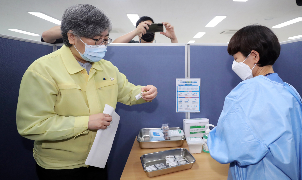 Jeong Eun-kyeong, the chief of the Korea Disease Control and Prevention Agency, (left) speaks with health care providers at a COVID-19 vaccination clinic in Cheongju, North Chungcheong Province, on Friday. (Yonhap)