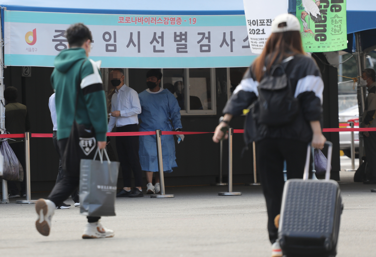 Travelers walk past a screening clinic for coronavirus tests in front of Seoul Station on Friday. (Yonhap)
