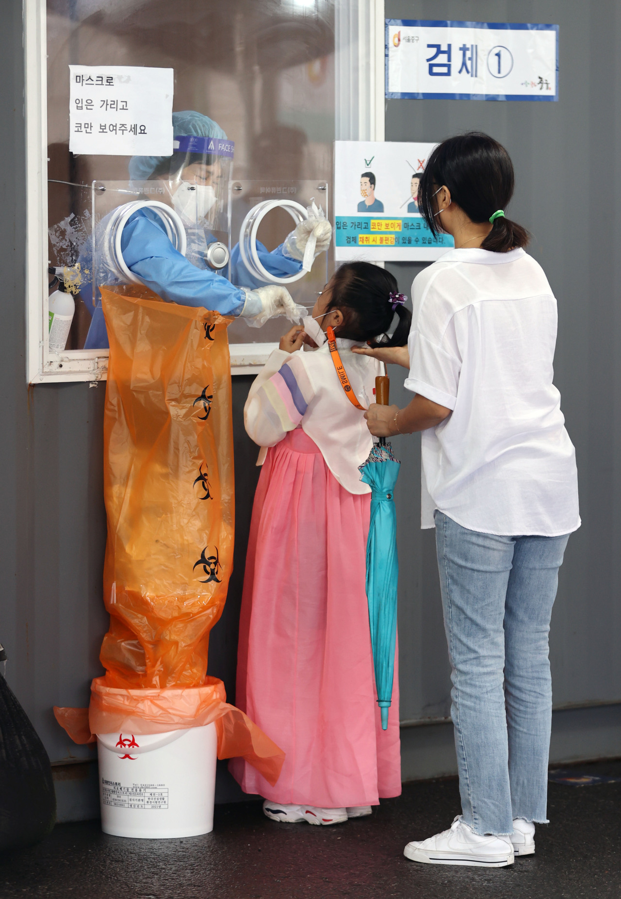 A child wearing traditional Korean clothing hanbok gets a COVID-19 test at a screening station in central Seoul on Chuseok, the Korean harvest holiday, on Tuesday(Yonhap)