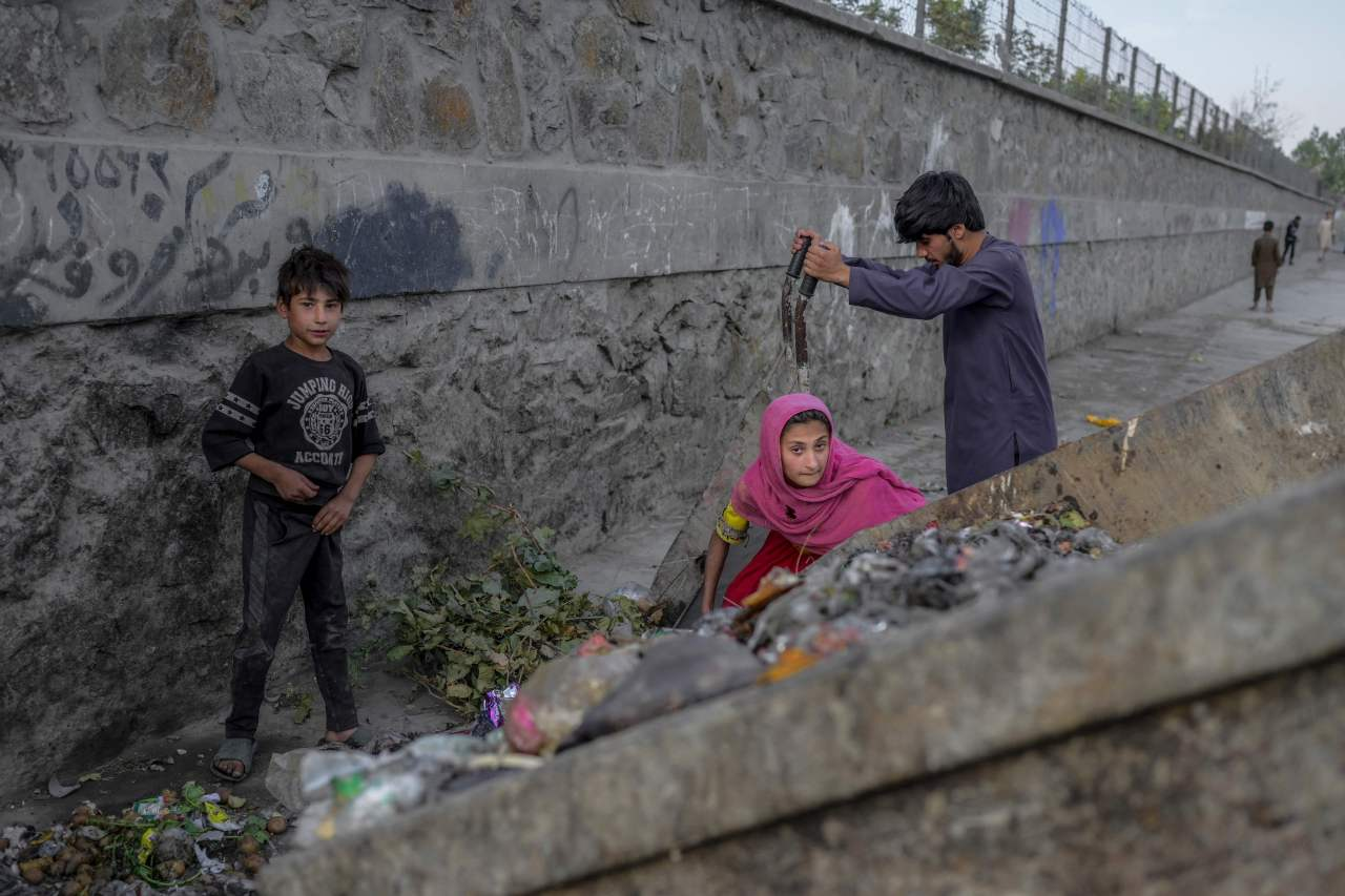 This AFP photo shows children collecting food and recyclable materials from garbage near the airport in Kabul on Tuesday. (AFP-Yonhap)