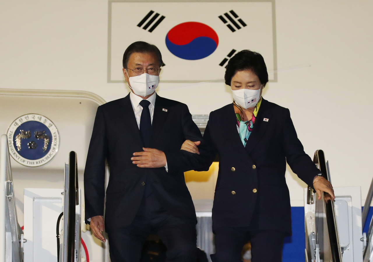 President Moon Jae-in (left) and First Lady Kim Jung-sook walk down the stairs as they arrived at Hickam Air Force Base in Hawaii Wednesday. (Yonhap)