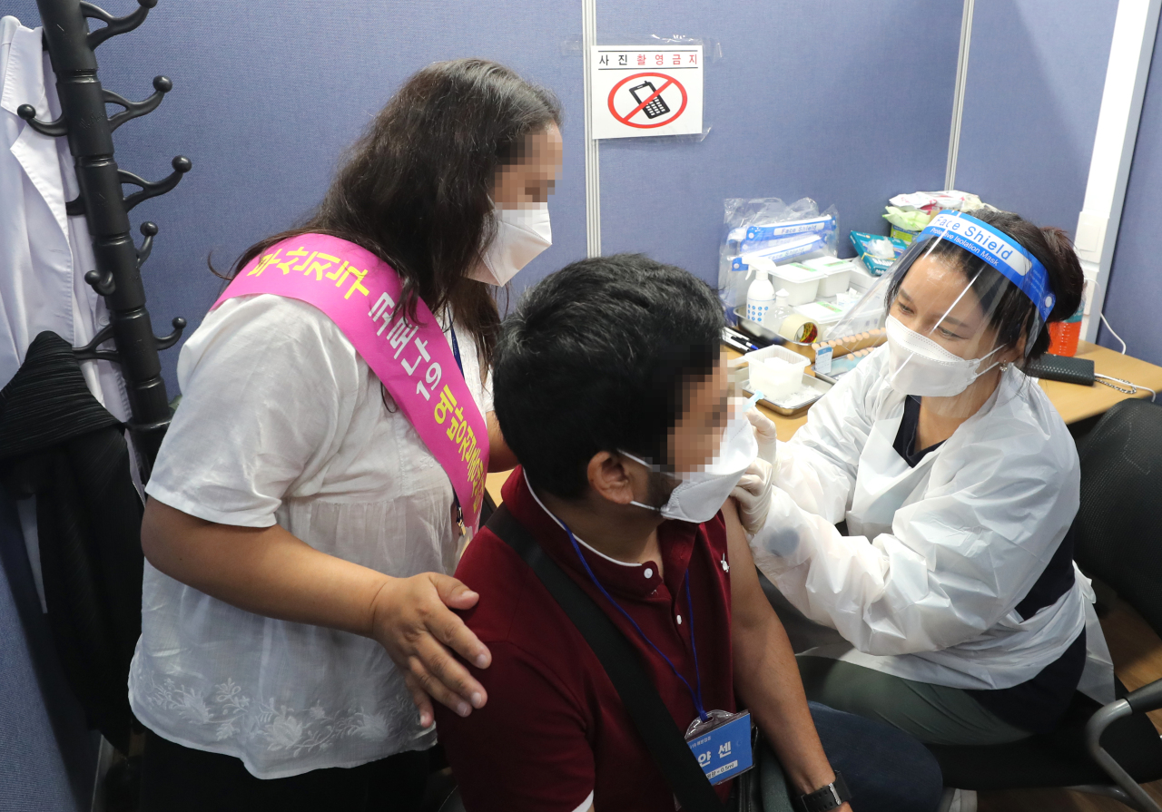 In this file photo, a foreigner receives a bracelet that shows his vaccination status after receiving a COVID-19 vaccine shot at a medical clinic in Busan, about 450 kilometers southeast of Seoul, on Sept. 14, 2021. (Yonhap)