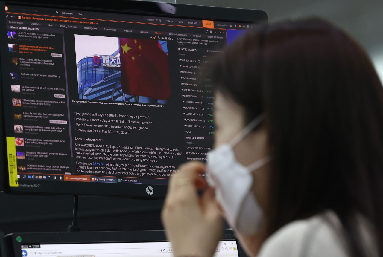 An employee reads an article on China's Evergrande debt crisis at Hana Bank's dealing room in Seoul on Thursday. South Korean authorities said they have been monitoring risks stemming from Evergrande's intense liquidity crisis as Beijing tightened regulations in its property sector to rein in excessive debt and speculation in recent months. (Yonhap)