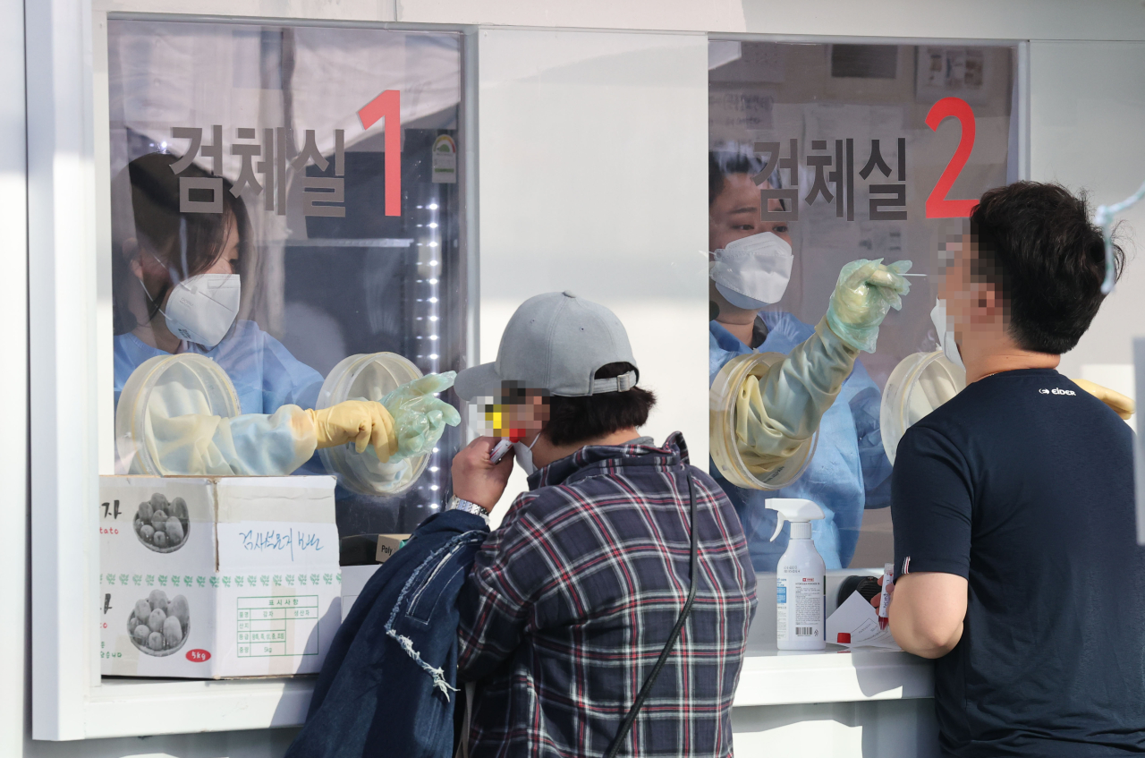 People receive coronavirus tests at a screening clinic in Seoul on Friday. (Yonhap)