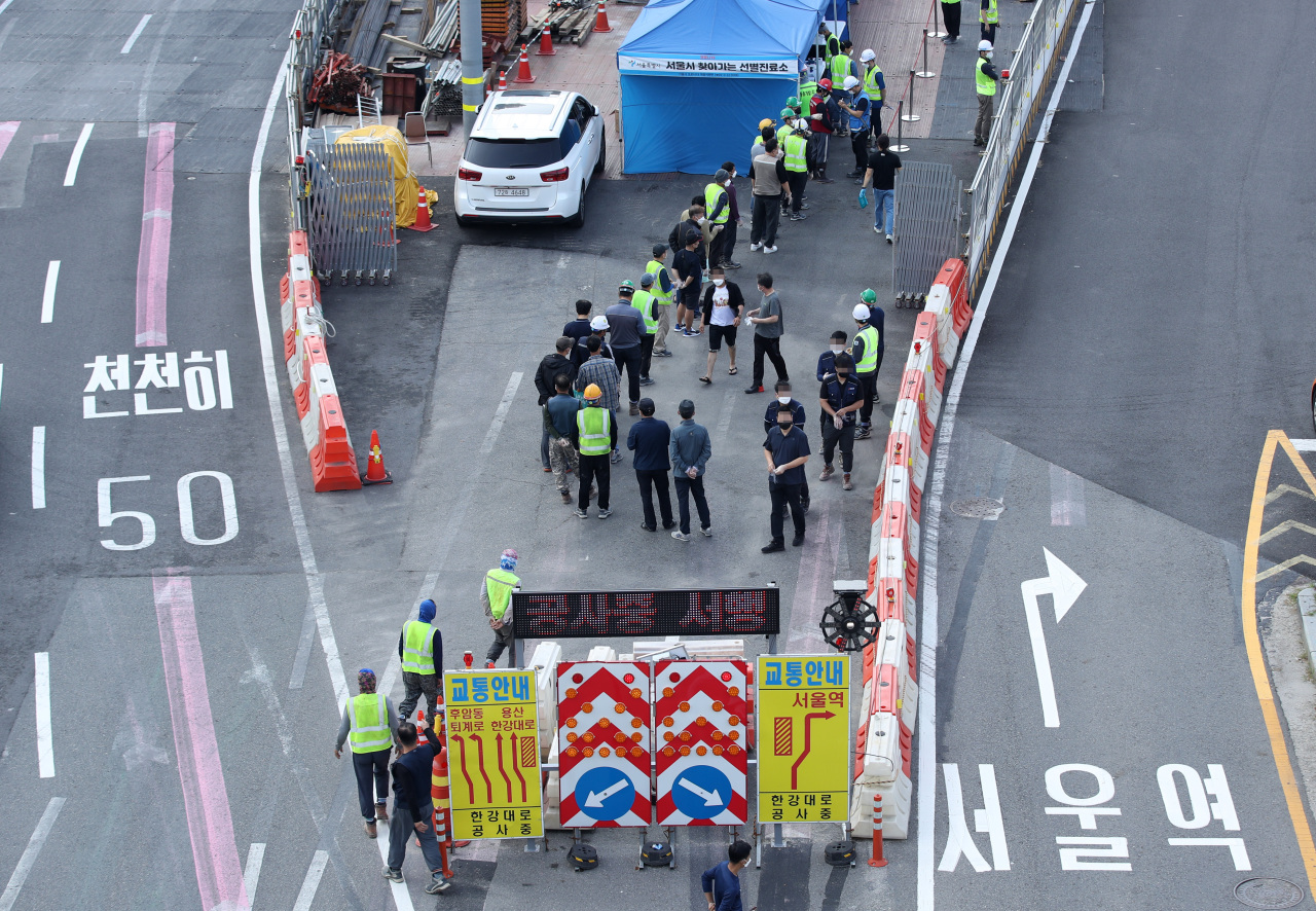 Construction workers line up to take virus tests at a screening center near Seoul Plaza in downtown Seoul on Friday. (Yonhap)