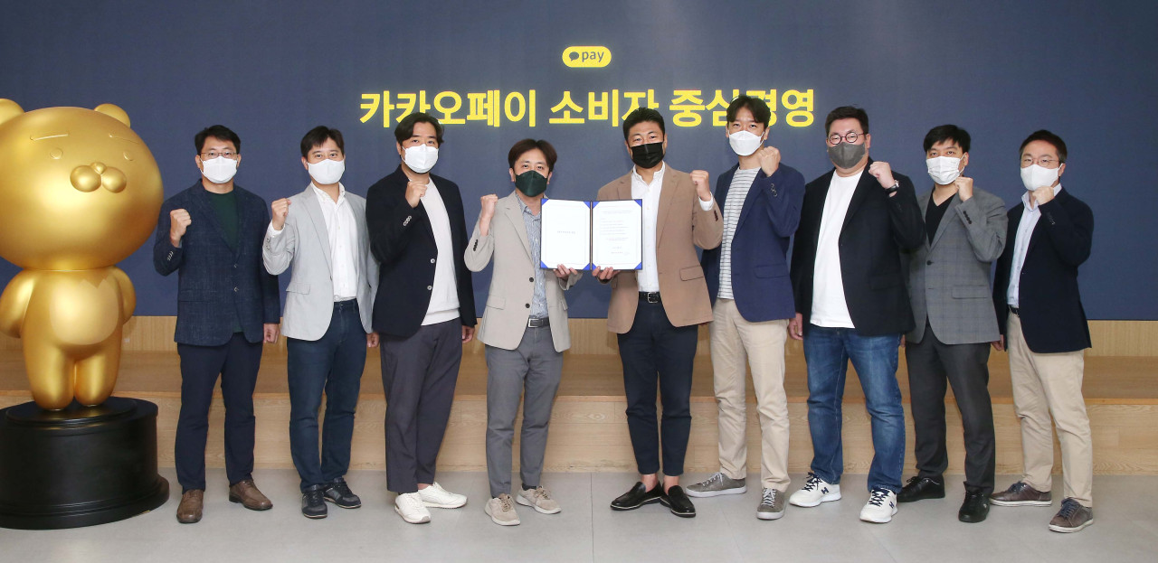 Kakao Pay Chief Executive Officer Alex Ryu (fifth from left) and staff pose for a photo during a ceremony held at its headquarters Friday. (Kakao Pay)