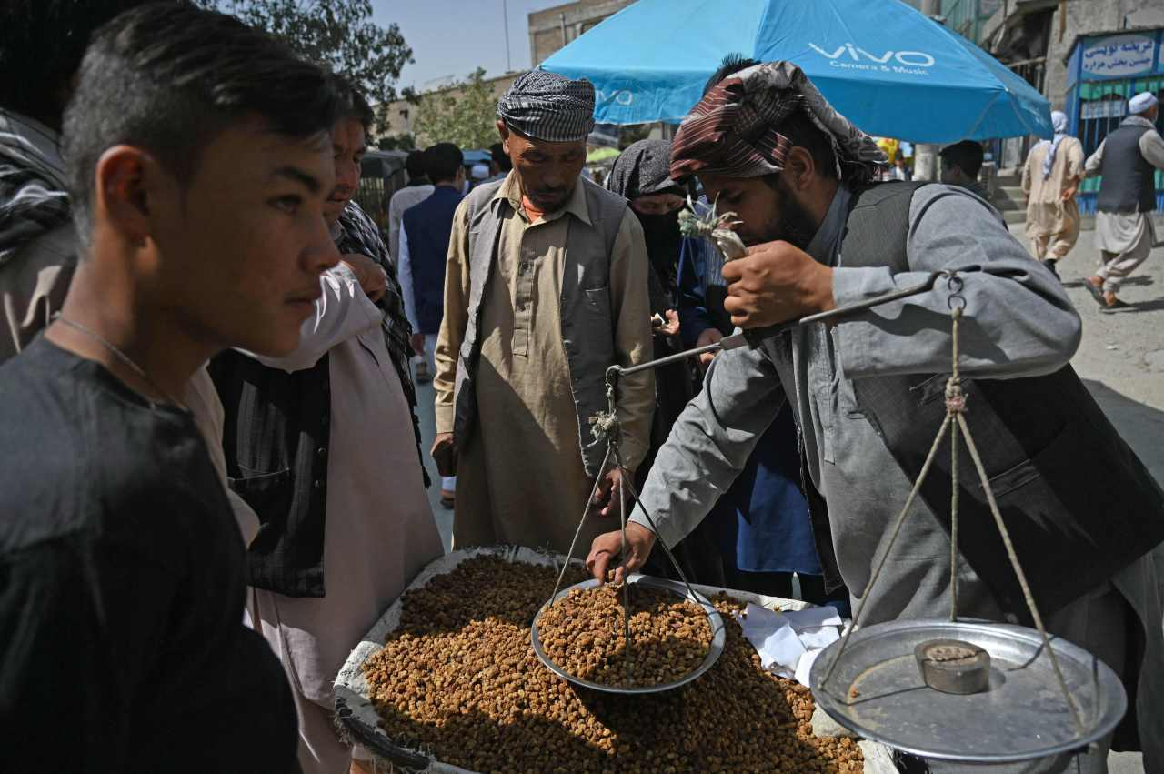 Members of the Hazara community buy dry mulberry at a market on the outskirts of Kabul on Sept. 10 (AFP-Yonhap)