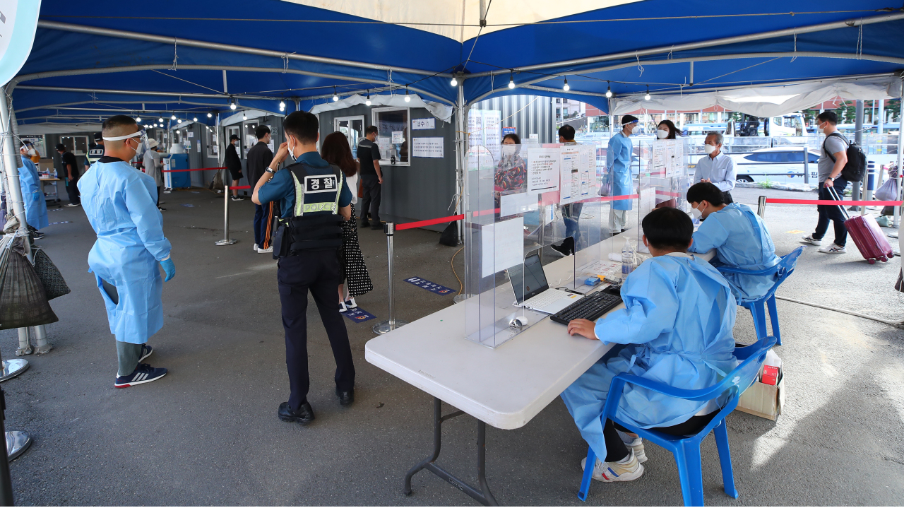 This photo taken Sunday morning shows people waiting at a testing clinic set up outside Seoul Station in the city`s central district. (Yonhap)