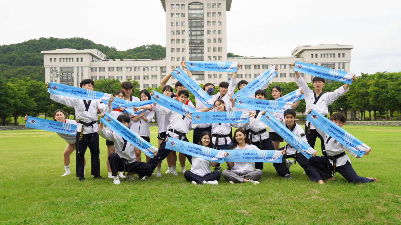 Students at Sun Moon University hold up signs to promote the Chungcheong area's bid to host the 2027 Summer World University Games. (Chungcheong Megacity Bid Committee)