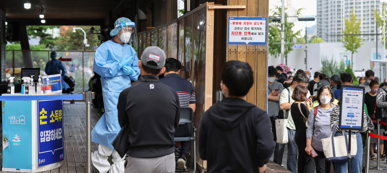A medical worker watches people standing in line to receive coronavirus tests at a screening clinic in Seoul's Songpa Ward on Monday. (Yonhap
