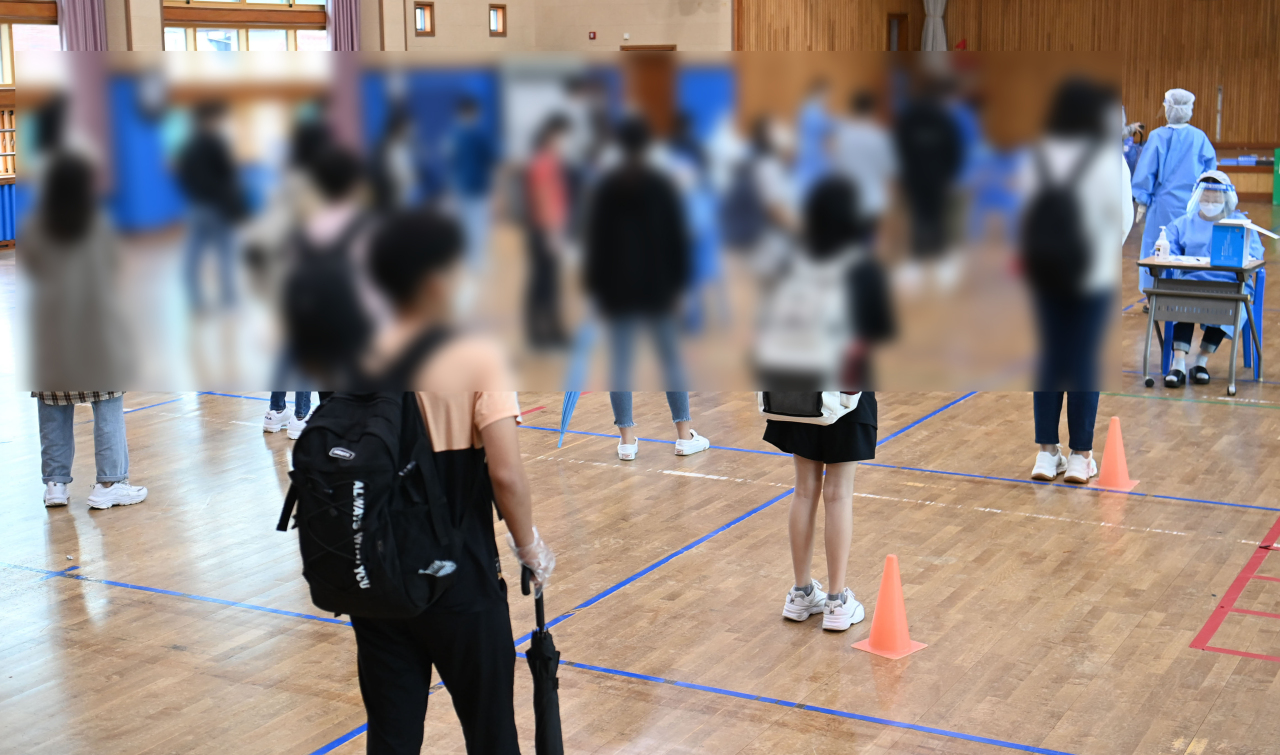 This Sept. 7, 2021, file photo shows students at a middle school in Gwangju, about 330 kilometers south of Seoul, taking a mass COVID-19 test after 13 infection cases broke out at the school. (Yonhap)