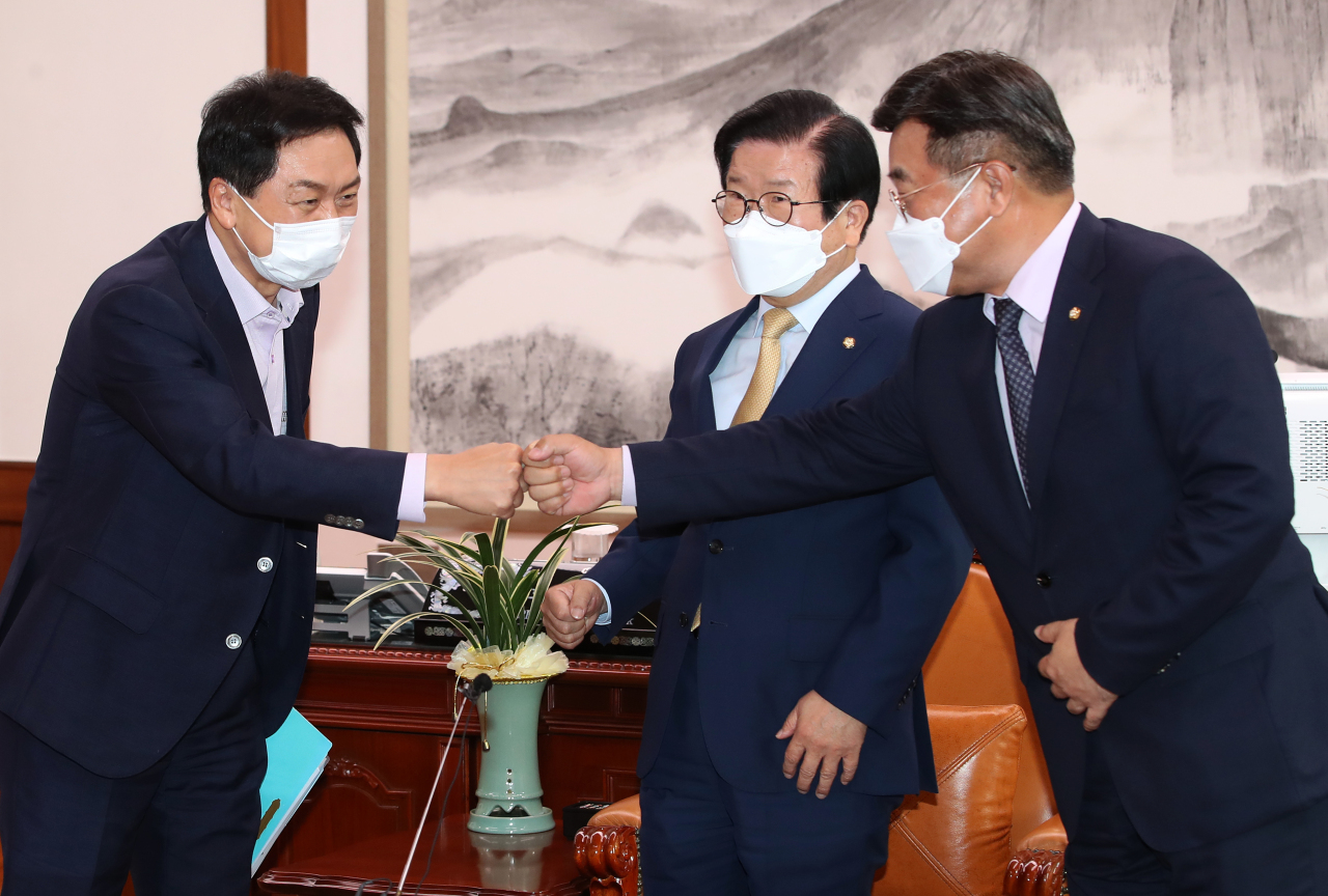 This image distributed by the National Assembly press corps shows Reps. Kim Gi-hyeon (L) and Yun Ho-jung (R), floor leaders of the People Power Party and Democratic Party, respectively, greeting each other during a meeting chaired by National Assembly Speaker Park Byeong-seug on Monday. (National Assembly Pess Corps)