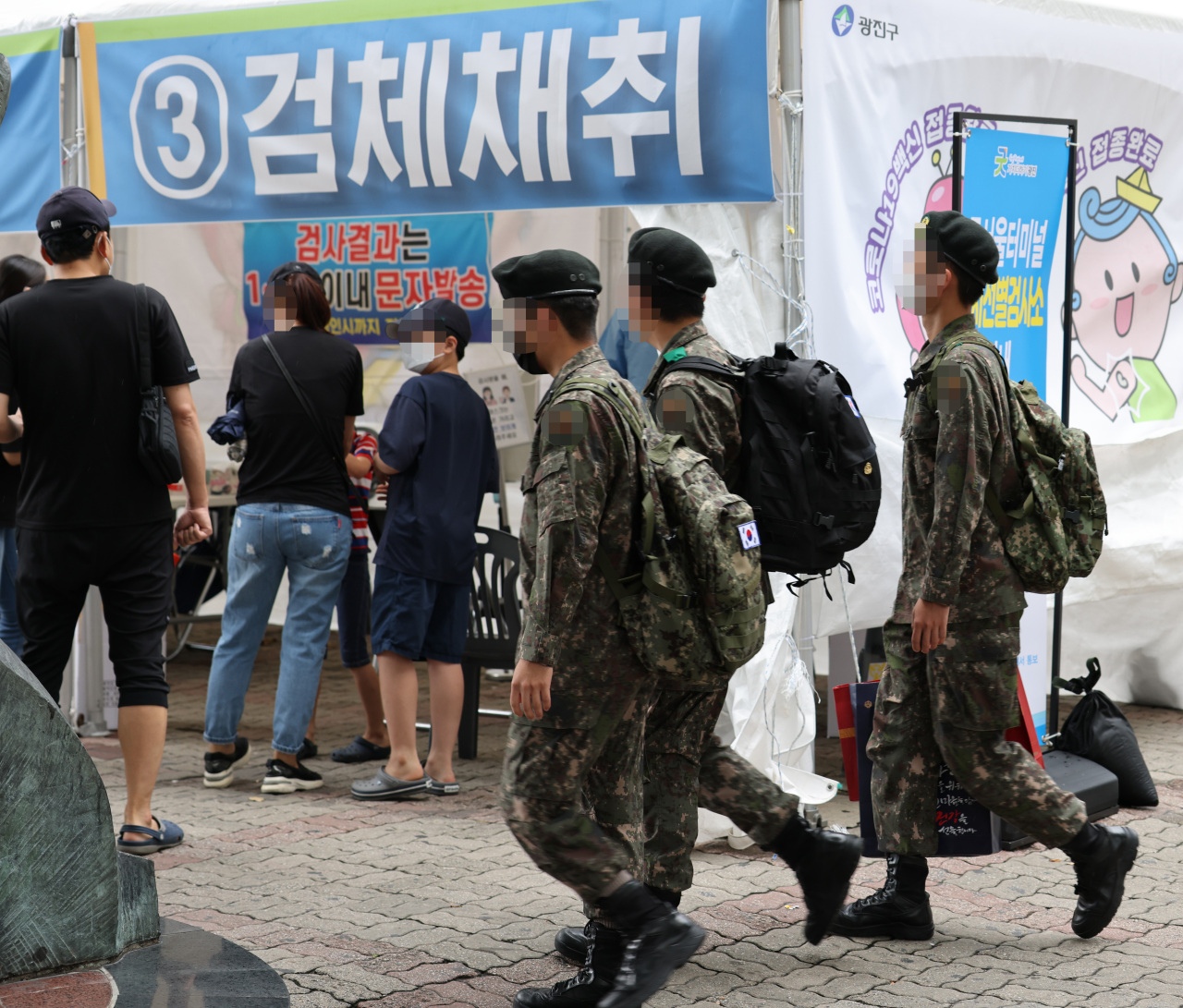 Service members enter a makeshift COVID-19 testing station set up at a bus terminal in Seoul last Wednesday. (Yonhap)