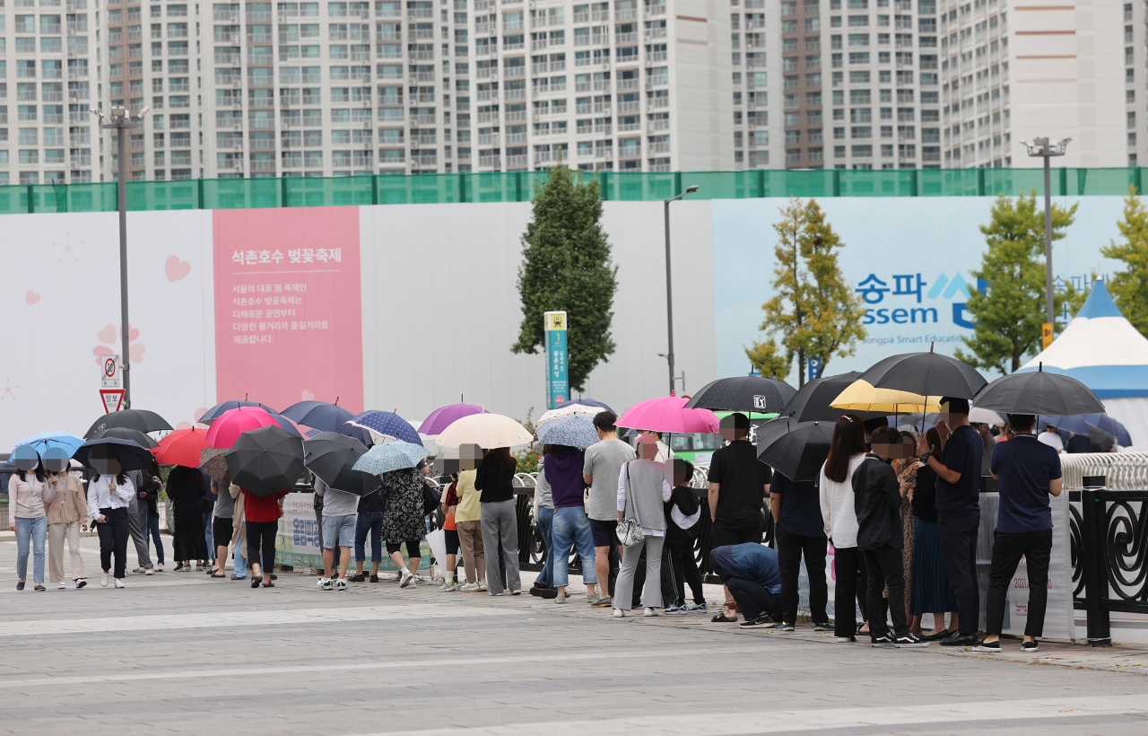 People stand in line to receive coronavirus tests at a screening clinic in Seoul's Songpa Ward on Tuesday. (Yonhap)