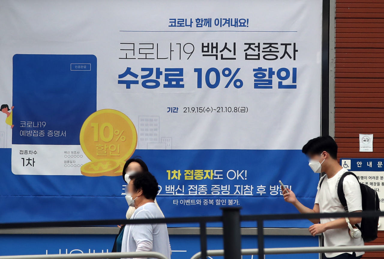 A banner informing of a 10 percent off tuition fee for vaccinated people is put up at a private educational institute in western Seoul on Tuesday. (Yonhap)