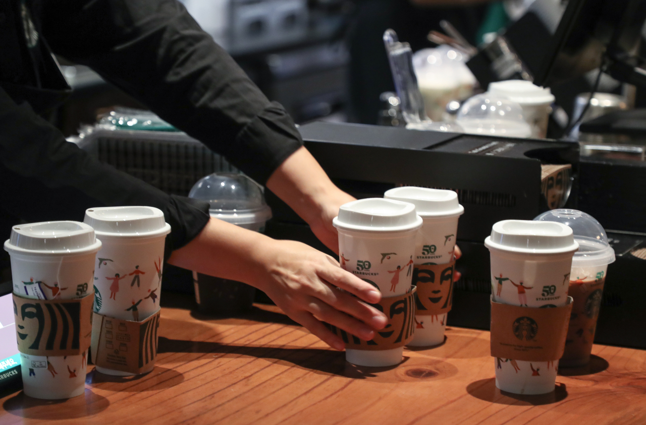 A Starbucks employee serves drinks in reusable plastic cups made as part of the coffee chain's 50th anniversary on Sept. 28th. (Yonhap)